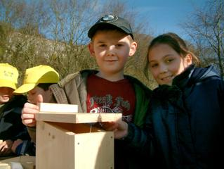 Children holding home made bird nest box
